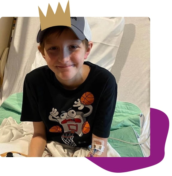 kid smiling sitting on a hospital bed