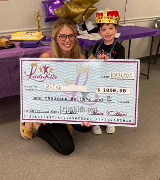 liea sitting with becket and a huge check